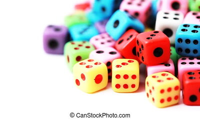 many colorful dice stacked in pile rotate on white...