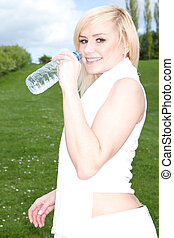 Young blonde drinking water outside