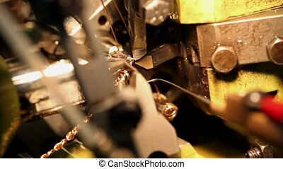 Cutter and wire in automatic chain-bending machine, closeup...