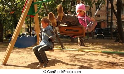Brother and little sister sway on swing at playground, sunny...