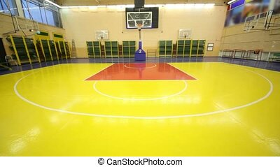 Inside lighted school gym hall with red yellow floor and basket, upward motion