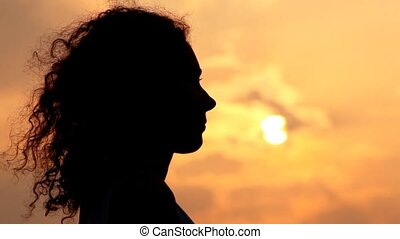 head smiling woman against sunset and cloud on sky - head...