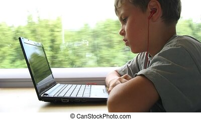 Boy in headphones watch video on notebook while travelling...