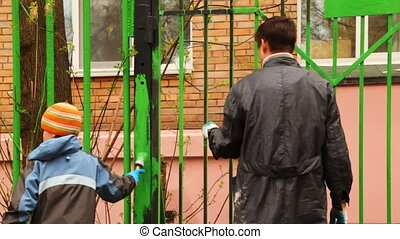 boy and father with paintbrush in hand carefully dye fence on community work day