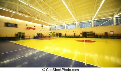 Lighted school gym hall with red yellow floor and baskets,...