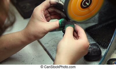 Man polishes piece of jewelry with grinding wheel, only...