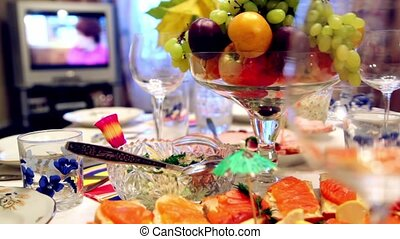 Bowl of fruit and different snacks on the table, the TV...