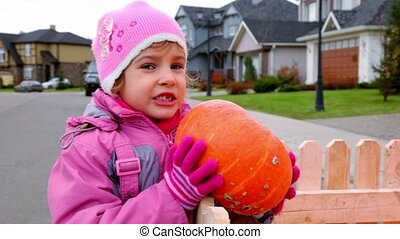 Little girl hold pumpkin leaned on wooden fence, at...