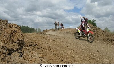 Spectators watch racers jump during enduro race - RAKOWO,...