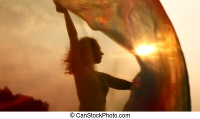 silhouette of woman with thin shawl in hands which waves on wind and gets to camera