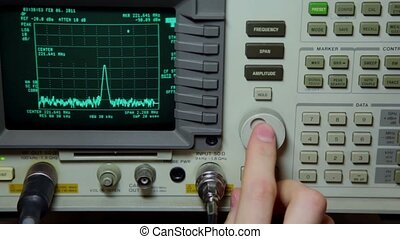 Hand push buttons and rotates knob on oscilloscope for old video repair