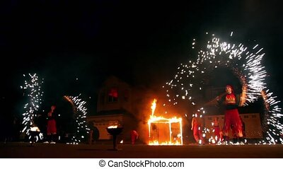 Two girls spin fireworks at fire show performance - New...