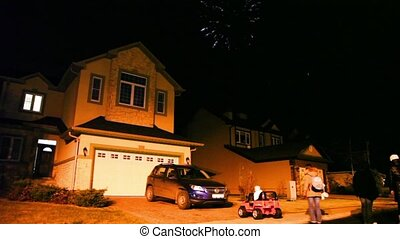 Few people watch fireworks at dark sky over house in cottage...