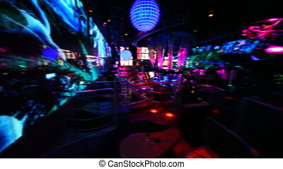 people in nightclub with bright LED illumination on walls,...