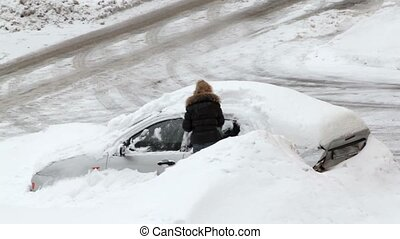 Woman digs out car littered with snow at winter day