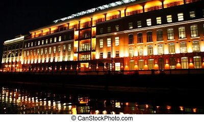large lighted building on bank of Moscow River at night