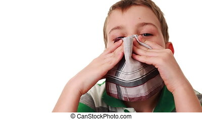 affected by cold boy wipes his nose with handkerchief and...