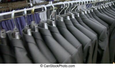 view of some identical jackets on hangers in shop - view of...