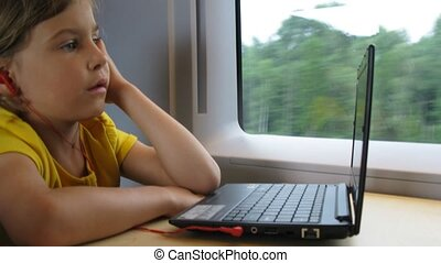 Girl in headphones watch video on notebook while travelling...