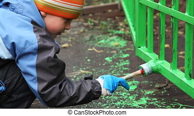 little boy with paintbrush in hand carefully dye fence on community work day