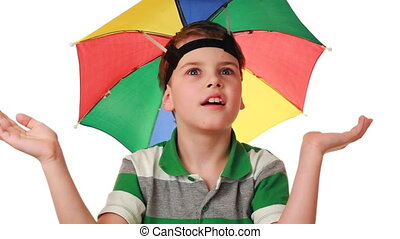 boy in cap as umbrella rainbow colors fun pretend that hiding from rain