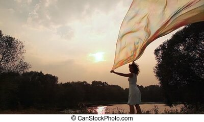 woman stands on bank of lake and holds shawl which fluttering