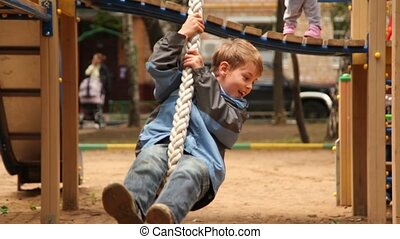 Boy sway on rope at playground at sunny autumn day