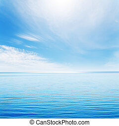light waves on blue sea and cloudy sky with sun
