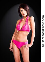 girl in pink bathing suit on black background