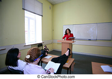 girl relaxing in the classroom is not paying attention to...