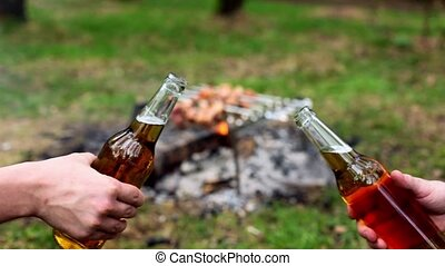 Two hands clink bottles with beer, at background of kebab on bonfire