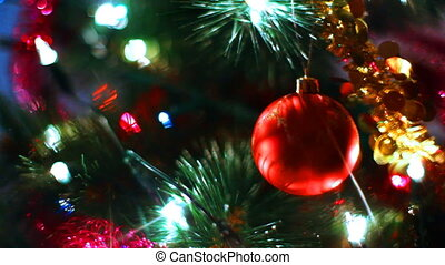 glass toy ball reflects light rays on Christmas tree among...