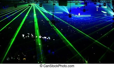Lot of people at rave party with green light lazer beam...