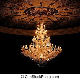 old chandelier hangs in ballroom