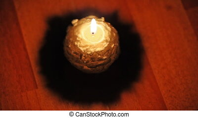 christmas candle stands on floor and flame sways air,...
