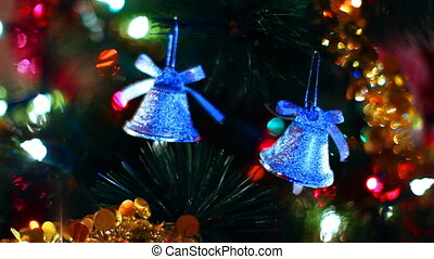two toy bells hang on Christmas tree among of blinking...