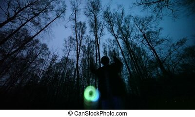 Man plays glowing toy in the dark forest, short exposure