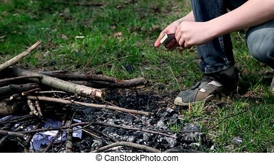 Little boy kindles bonfire with match, only legs are visible