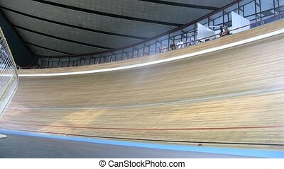 Bicyclists compete on bicycle track in sports complex, time...