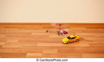 toy car rides on floor, small helicopter flying over