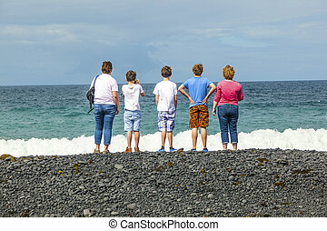 family watches the waves at the black volcanic beach