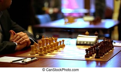 Chess starting position on board closeup, paper notebook on...