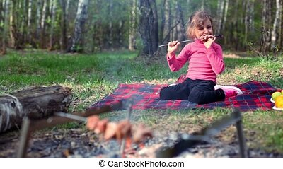 Little girl, sit on grass cover by plaid and eats kebab on skewers
