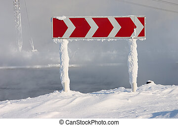 Frozen and snowed guide road sign of turn on a background of a fog above water