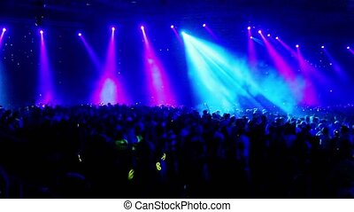 Crowd at rave party, view from behind, large hall full of...
