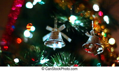 two toy bells hang on Christmas tree among of blinking colored garlands