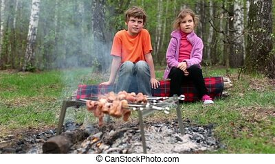 Boy and little girl sit on log, fresh meat cooking on embers...