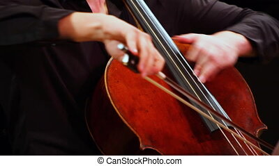 expressive man plays cello sitting on stage
