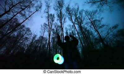 Man plays glowing toy in the dark forest, long exposure