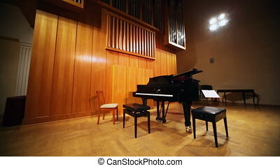 grand piano on stage near organ